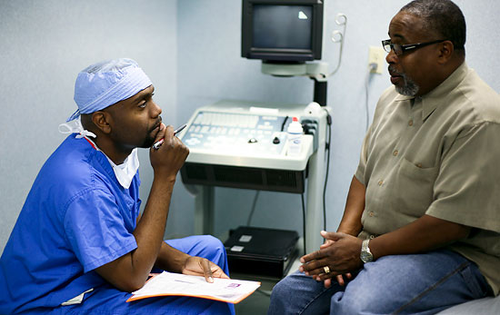 Paul Alphonse Jr., MD '98, checks in with patient Vincent Alston at the Midtown Urology Surgical Center in Atlanta