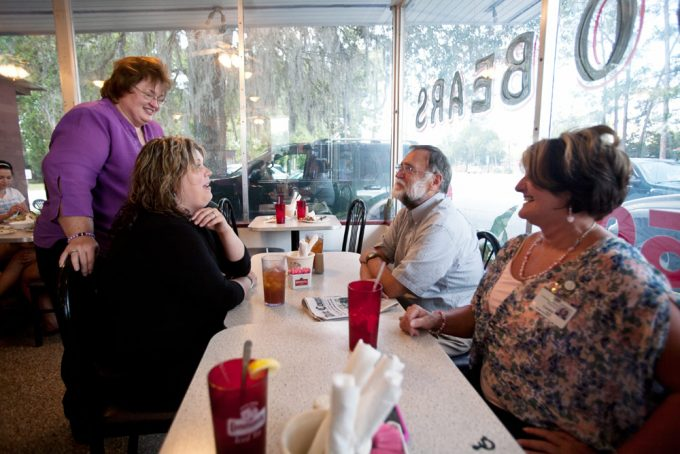 Dr. Larry Rooks and Gredel Buzbee, UF Old Town's practice manager, chat with local residents — and patients of Rooks — Mariah Owen and Cindy Bellot over lunch at Elaine's in Cross City. Owen's mother owns Elaine's and Bellot is the supervisor of the Dixie County Public Library, where Rooks has played his banjo and sung for children's programs. Photo by Maria Belen Farias