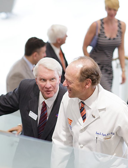Dr. Steven M. Scott, left, chair of the UF Board of Trustees, and Dr. David S. Guzick, senior vice president for health affairs at UF and president of UF Health, walk together during the building dedication for the Harrell Medical Education Building.